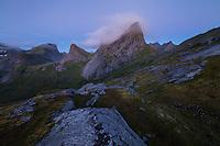 Twilight clouds swirl over dramatic summit of Kråkhammartind mountain peak, Moskenesøy, Lofoten Islands, Norway