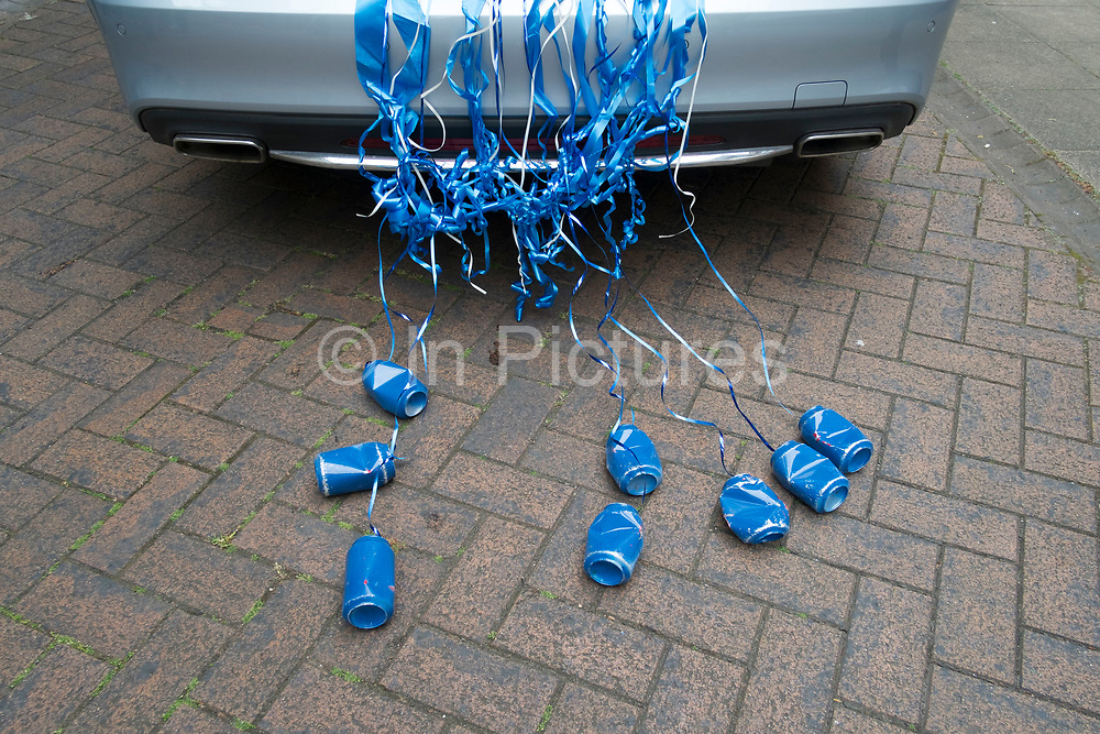 Blue cans attached to the back of a wedding car in Warwick, England, United Kingdom. This is a popular way to see the newlyweds off, tin cans rattling behind their car. The tradition originated as a way of keeping evil spirits away from the happy couple.