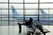 A traveler waits on a bench in front of a window overlooking parked China Eastern passenger jets at the Shanghai Hongqio Airport in Shanghai, China, on Nov. 21 2011. A mixture of pollution and foggy weather are frequently causing low visibility that delays air travel.