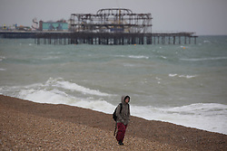 © Licensed to London News Pictures.  03/05/2021. Brighton, UK. A member of the public walks along cost line of Brighton Beach in East Sussex, following The May Day, bank holiday as forecasts predict strong winds and rain for the coming week. Photo credit: Marcin Nowak/LNP