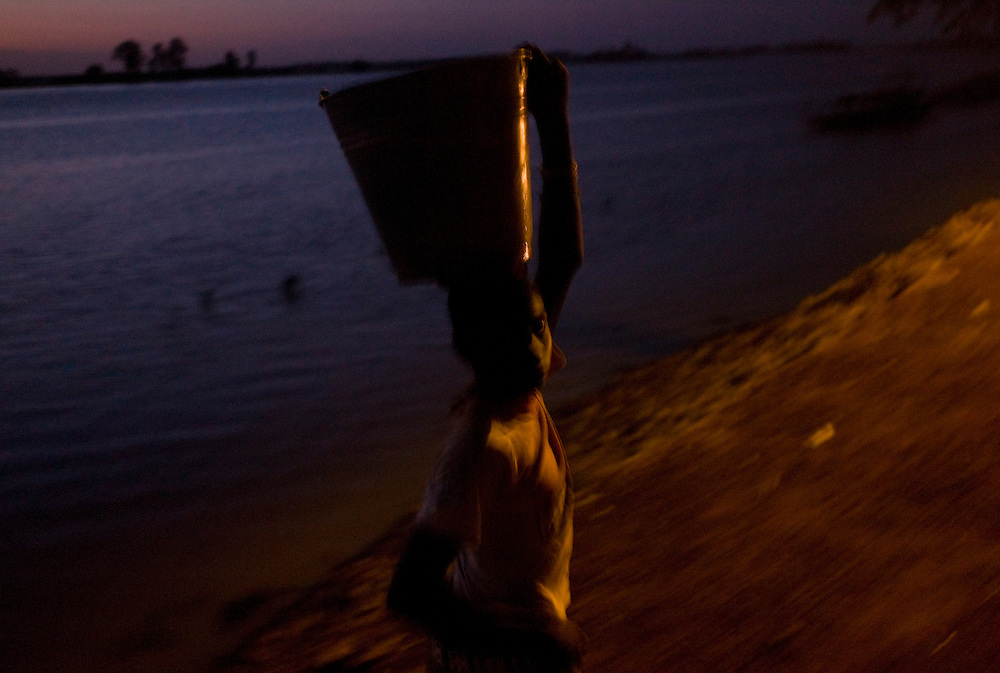 A boy carrying a bucket walks by the riverside ate dusk. At the confluence of the Niger and the Bani rivers, between Timbuktu and Segou, Mopti is the second largest city in Mali, and the hub for commerce and tourism in this west-african landlocked country.