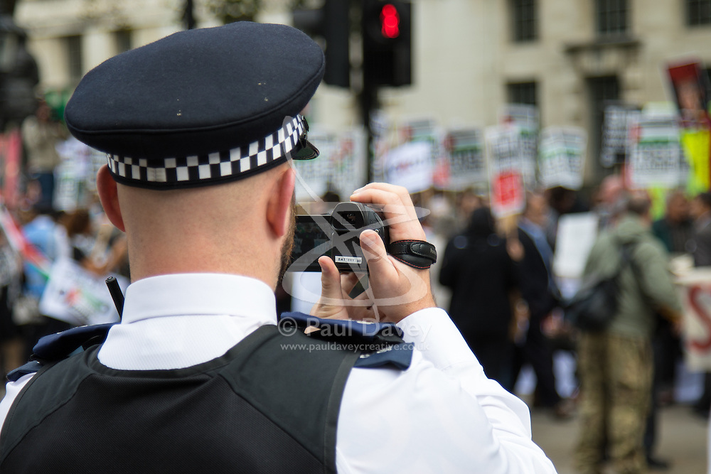 Whitehall, London, September 9th 2015.  A Police officer films protesters as pro Palestinian and Israeli counter-protesters clash in Whitehall as the Palestinian Solidarity campaign demands the arrest of Israel's PM Benyamin Netanyahu for war crimes in the 2014 war with Palestinians in Gaza.  // Contact: paul@pauldaveycreative.co.uk Mobile 07966 016 296