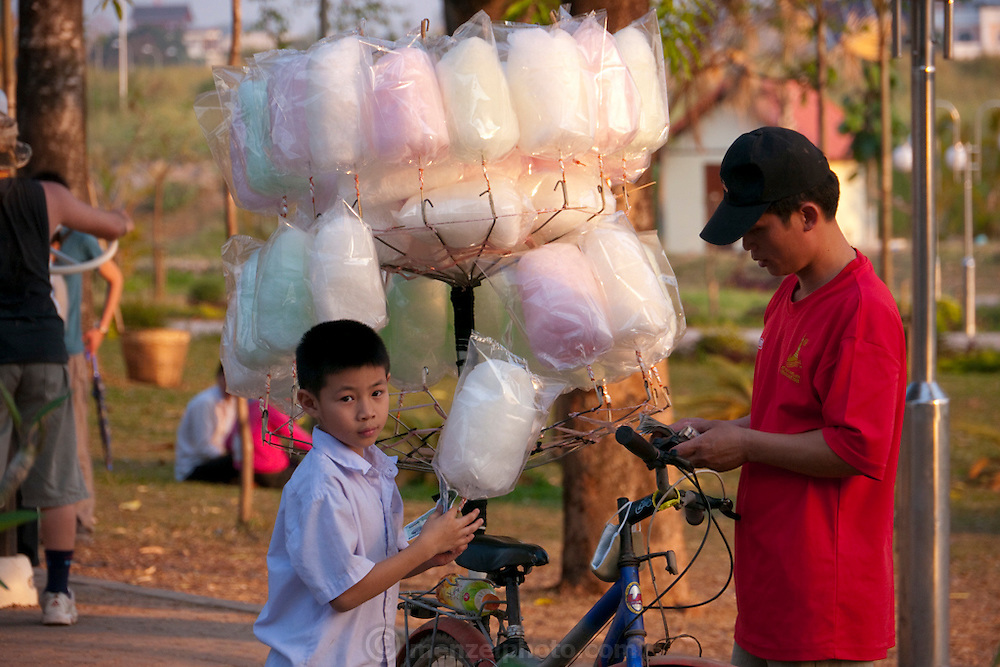 Vientiane, Laos. Boy buying cotton cany in the park with exercise equipment on the banks of the Mekong River on Fa Ngum Road.