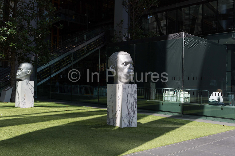 An office worker makes calls near sculpture entitled Numen Shifting Votive One & Two by Thomas J Price outside the Leadenhall Building during the 2018 heatwave in the City of London, the capitals financial district, on 24th July 2018, in London, England.