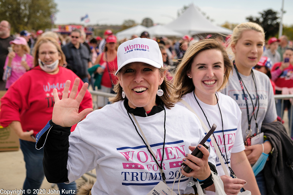 14 OCTOBER 2020 - DES MOINES, IOWA: Women walk into a reelection rally for President Donald Trump. About10,000 people were expected at the Des Moines International Airport for a campaign rally supporting the reelection of President Donald Trump. Trump spoke at the rally, despite testing positive for COVID-19 less than three weeks ago. The rally did not meet the CDC guidelines for a safe gathering in the time of Coronavirus and violated Iowa's health emergency declarations barring gatherings of more than 25 people. This week Iowa exceeded 101,000 cases of COVID-19 and a surge in hospitalizations for COVID-19.      PHOTO BY JACK KURTZ