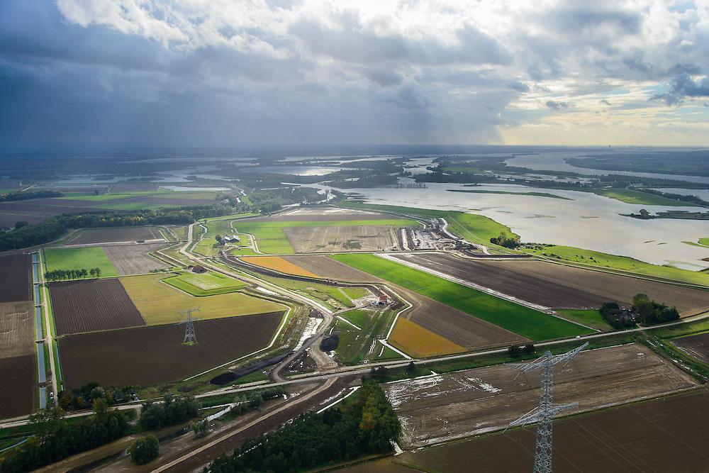 Nederland, Noord-Brabant, Werkendam, 23-10-2013; Ruimte voor de Rivier project Ontpoldering Noordwaard. Het deel rechtsboven is reeds ontpolderd, onder het gedeelte in ontwikkeling waar boerderijen en particuliere huizen op nieuw opgeworpen terpen gebouwd worden. Midden in beeld een nieuwe dijk, hierlangs zal het water stromen, vanaf rivier de Nieuwe Merwede, de bestaande dijk krijgt een instroomopening.<br /> Delen van de polder (links) wordt ontpolderd en de dijken worden verlegd en/of verlaagd waardoor bij hoogwater het rivierwater ook door de polder sneller weg kan stromen richting zee. Gevolg van de ingrepen is ook dat de waterstand verder stroomopwaarts zal dalen.<br /> National Project Ruimte voor de Rivier (Room for the River) <br /> By lowering and / or moving the dike of the Noordwaard polder the area will become subject to controlled inundation and function as a dedicated water detention district. Houses and farmhouses will be constructed on new dwelling mounds. <br /> luchtfoto (toeslag op standard tarieven);<br /> aerial photo (additional fee required);<br /> copyright foto/photo Siebe Swart