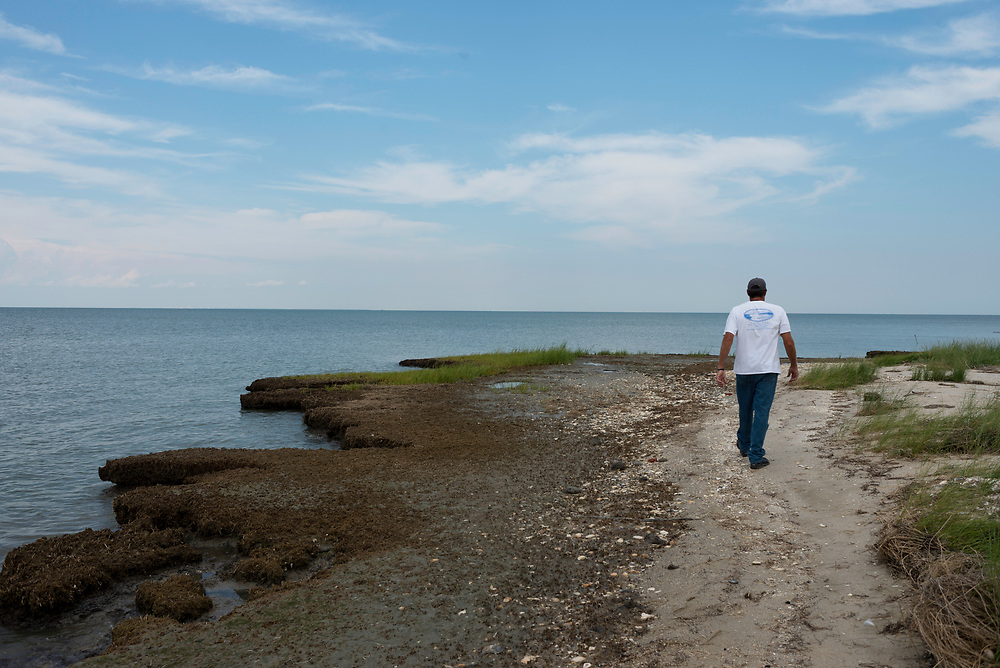 """August 4, 2017 - Tangier Island, VA - <br /> Mayor James """"Ooker"""" Eskridge tours """"The Uppards,"""" a previously habited portion of Tangier Island that is today very diminished in size due to erosion.  A few of the old homes from this area of the island have been moved to the more inhabited part of the island, across a widening waterway once accessible by bridge. That bridge no longer exists. .  Photo by Susana Raab/Institute"""