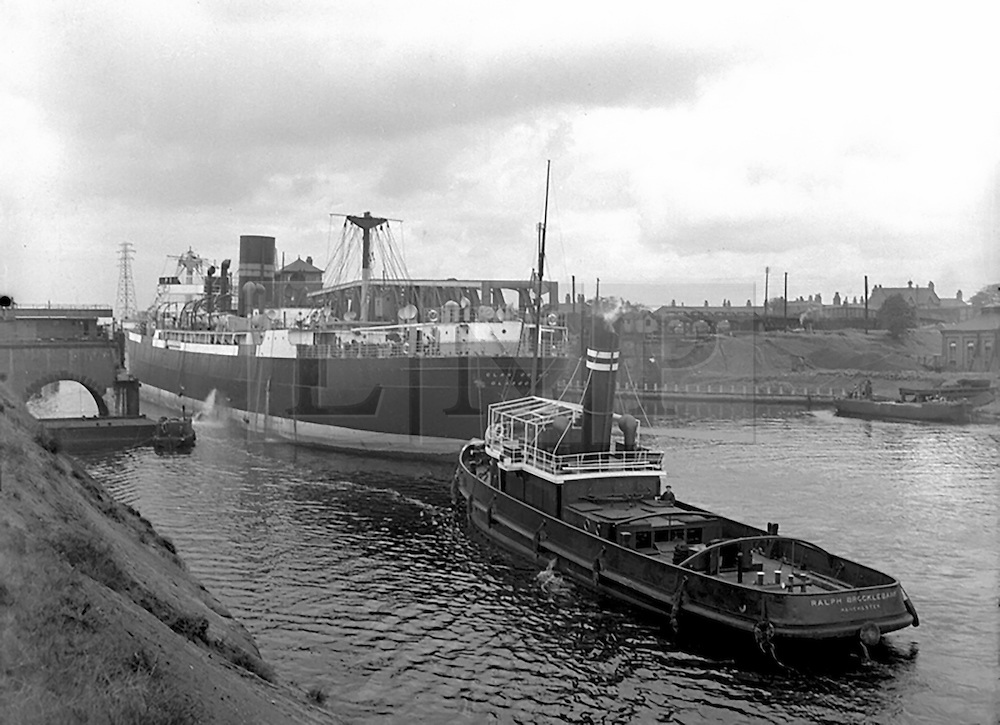 """© Licensed to London News Pictures. 04/05/2016. Birkenhead UK. Collect picture shows the Ralph Brocklebank (daniel Adamson) working in Manchester (date unknown). The Daniel Adamson steam boat has been bought back to operational service after a £5M restoration. The coal fired steam tug is the last surviving steam powered tug built on the Mersey and is believed to be the oldest operational Mersey built ship in the world. The """"Danny"""" (originally named the Ralph Brocklebank) was built at Camel Laird ship yard in Birkenhead & launched in 1903. She worked the canal's & carried passengers across the Mersey & during WW1 had a stint working for the Royal Navy in Liverpool. The """"Danny"""" was refitted in the 30's in an art deco style. Withdrawn from service in 1984 by 2014 she was due for scrapping until Mersey tug skipper Dan Cross bought her for £1 and the campaign to save her was underway. Photo credit: Andrew McCaren/LNP ** More information available here http://tinyurl.com/jsucxaq **"""