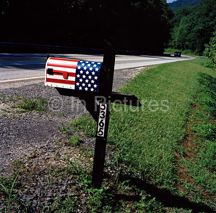 Mail-box on the road leading into Robbinsville, North Carolina. Although this picture is typical of the road side view one gets when driving through the US. The US flag depicted in this context reflects the increased visibility of the stars and stripes post 9/11 and evokes a more sinister interpretation of this picture.