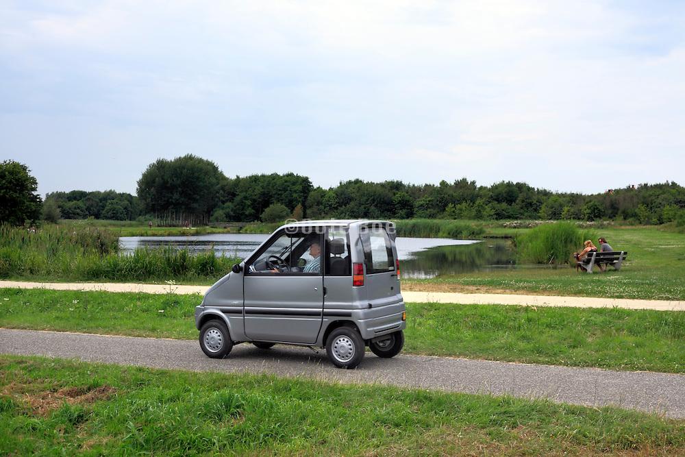 Dutch little handicap car driving in nature park near Amsterdam Holland