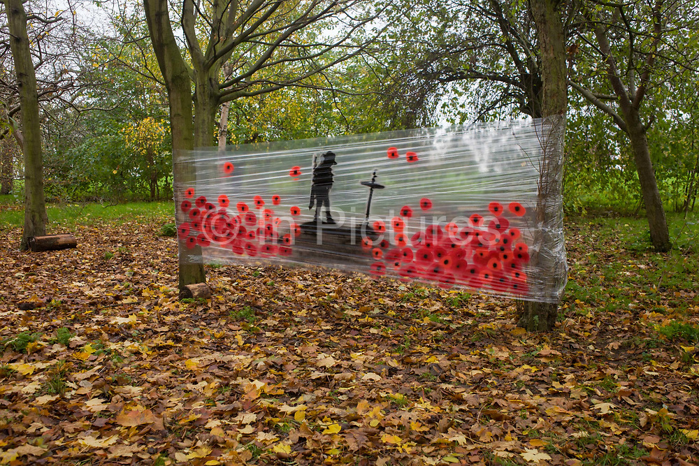 A makeshift artistic memorial to those fallen in past wars, stretched across trees in Hilly Fields, Ladywell, south London. Among brown autumn leaves is this temporary shrine in memory of the casualties in the London borough of Lewisham. A lone soldier stands on a mound alongside a cross, surrounded by the depiction of poppies perhaps created by a local artist. Over a million military personnel were killed in WW1.