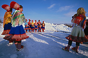 Family members pose for photographs and video recordings after the confirmation of a Sami girl in Kautokeino, northern Norway. The Sami living in Kautokeino hold confirmations and other life cycle ceremonies at Easter time, after which the reindeer herders move with their herds to the Atlantic coast for summer pasture.  The traditional tunics that the Saami women wear are made of wool, the scarves of silk and the shoes and trousers of reindeer fur. The brooches holding the scarves together in front are made of silver.