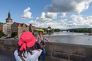 An Asian tourist is getting photographed by her fellow traveller on Charles Bridge. The Charles Bridge (Czech: Karlův most) is a famous historic bridge that crosses the Vltava river in Prague, Czech Republic and is probably the Nr.1 tourists magnet in the city.