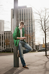 Teenager waiting for someone and listen to music in the street, Bavaria, Germany