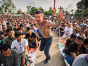 """07 MARCH 2015 - NAKHON CHAI SI, NAKHON PATHOM, THAILAND: A man charges the stage channeling the power of his spiritual tattoo at the Wat Bang Phra tattoo festival. Wat Bang Phra is the best known """"Sak Yant"""" tattoo temple in Thailand. It's located in Nakhon Pathom province, about 40 miles from Bangkok. The tattoos are given with hollow stainless steel needles and are thought to possess magical powers of protection. The tattoos, which are given by Buddhist monks, are popular with soldiers, policeman and gangsters, people who generally live in harm's way. The tattoo must be activated to remain powerful and the annual Wai Khru Ceremony (tattoo festival) at the temple draws thousands of devotees who come to the temple to activate or renew the tattoos. People go into trance like states and then assume the personality of their tattoo, so people with tiger tattoos assume the personality of a tiger, people with monkey tattoos take on the personality of a monkey and so on. In recent years the tattoo festival has become popular with tourists who make the trip to Nakorn Pathom province to see a side of """"exotic"""" Thailand.   PHOTO BY JACK KURTZ"""