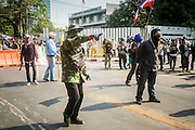 """01 FEBRUARY 2014 - BANGKOK, THAILAND:  Anti-government protestors taunt voters who tried to get past them to vote. The anti-government protestors also had guns and threatened to shoot people who wanted to vote. Thais went to the polls in a """"snap election"""" Sunday called in December after Prime Minister Yingluck Shinawatra dissolved the parliament in the face of large anti-government protests in Bangkok. The anti-government opposition, led by the People's Democratic Reform Committee (PDRC), called for a boycott of the election and threatened to disrupt voting. Many polling places in Bangkok were closed by protestors who blocked access to the polls or distribution of ballots. The result of the election are likely to be contested in the Thai Constitutional Court and may be invalidated because there won't be quorum in the Thai parliament.   PHOTO BY JACK KURTZ"""