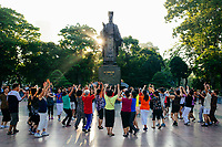 Morning yoga beneath Ly Thai To statue on Hoam Kiem Lake in downtown Hanoi, Vietnam.