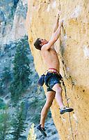 A male rock climber climbing a rock face at Smith Rock State Park Oregon USA