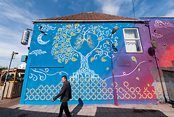 © Licensed to London News Pictures; 23/09/2021; Bristol, UK. An all-female Muslim street art collective called Peace of Art have painted a mural on the side of the Thali restaurant in Easton, Bristol, to highlight the dangerous levels of air pollution in the area. The mural stretches the length of the building with a tree showing a pair of lungs with the left side healthy and the right side affected by pollution from the city and with the word 'Breathe' on the end. Photo credit: Simon Chapman/LNP.