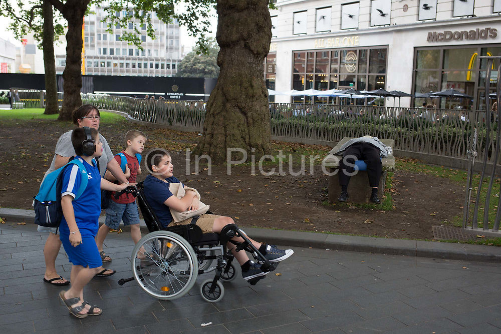 A disabled boy and his family walk past a sleeping man, on 31st July 2017, in Leicester Square, London, England.