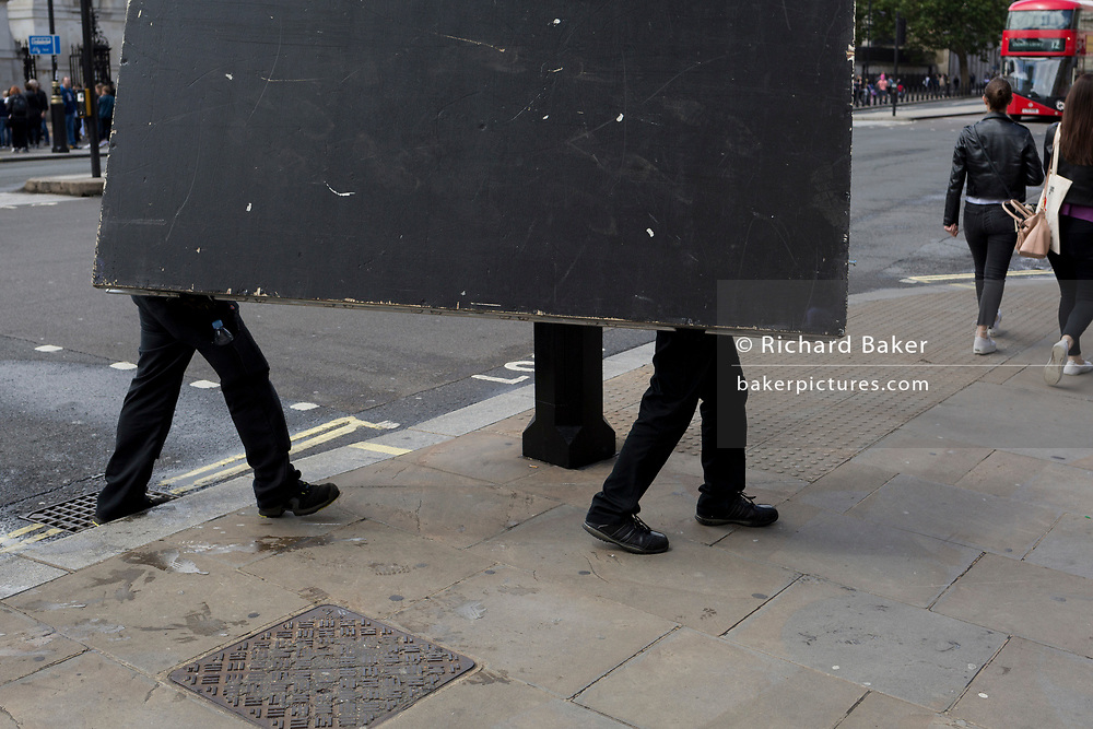 Two workmen carry a large board before a special event at the Banqueting House on Whitehall in Westminster, on 15th June 2019, in London, England.