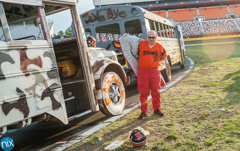 Tim Farrar, principal from Northwest Cabarrus Middle, puts on his fire suite during the Principal School Bus Slobberknocker at Charlotte Motor Speedway Tuesday night during the Summer Shootout.