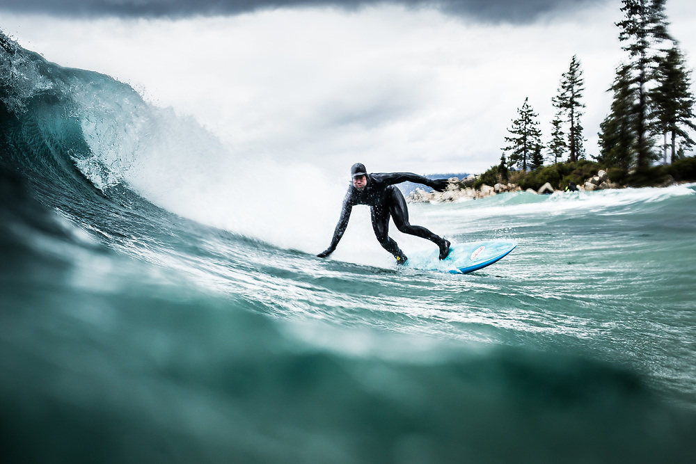 A man surfing on a stormy Lake Tahoe day at Sand Harbor near Incline Village, NV.