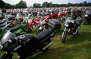 A field full of parked motorbikes at. large rally, Suffolk show ground, England, UK c 2000