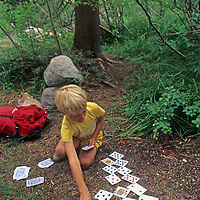 A youngster plays solitaire during a rest while backpacking in California's Sierra Nevada.
