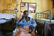 Sinethemba, a 12-year old African boy has Steven Johnson Syndrome; a life-threatening skin condition often triggered as an allergic reaction to  HIV medication.  He sits in a chair while receiving medication through a naso-gastric tube. He is a patient of Baragwanath hospital in Johannesburg, South Africa.  Baragwanath is the third biggest hospital in the world.