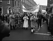 "Irish Theatre Industry Protest at Leinster House.1983.07.12.1983.12.07.1983.7th December 1983...With the imposition of a 23% V.A.T.rate on theatre tickets, the theatre industry was feeling the strain. Maureen potter and Brendan Grace aka ""Bottler"" led the protest to the gates of Leinster House Dublin...Image of Maureen,carrying banner,and her theatre colleagues lead the protest up Kildare St,Dublin to the Dail."