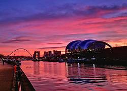 © Licensed to London News Pictures. 02/01/2020. Newcastle, UK. A bright sunrise on a winter morning over the River Tyne in Newcastle, north east England, with the Sage music hall (right) and Millennium Bridge (left) pictured. Photo credit: Colin Scarr/LNP