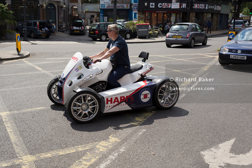 A hairdresser's ATV GG Quadster, a 4-wheel motorbike, turns across a yellow grid across the junction at Herne Hill in south London, on 24th May 2019, in London, England.