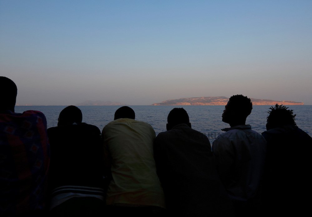 Migrants look out from the Medecins san Frontiere (MSF) rescue ship Bourbon Argos as it approaches Trapani, on the island of Sicily, Italy, August 9, 2015.  Some 241 mostly West African migrants on the ship arrived on the Italian island of Sicily on Sunday morning, according to MSF.<br /> REUTERS/Darrin Zammit Lupi <br /> MALTA OUT. NO COMMERCIAL OR EDITORIAL SALES IN MALTA