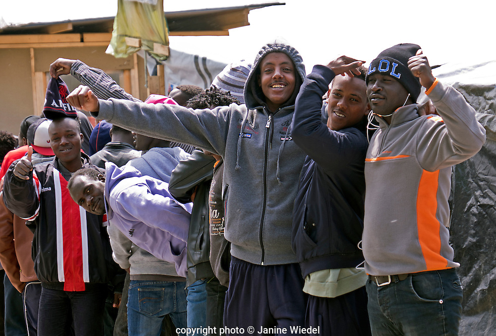 Peopel waiting in a queue for distribution of supplies and clothes in The Calais Jungle Refugee and Migrant Camp in France