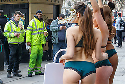 © Licensed to London News Pictures. 17/02/2017. London, UK. Members of public photograph three nearly naked demonstrators, wearing lingerie and crocodile masks and protesting against use of exotic animals in fashion industry outside London Fashion Week in central London on 17 February 2017. Photo credit: Tolga Akmen/LNP