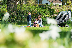 © Licensed to London News Pictures. 13/04/2014. London, UK. A woman sits with children in the grounds.  People enjoy the morning sunshine at Chiswick House in West London today 13th April 2014. Photo credit : Stephen Simpson/LNP