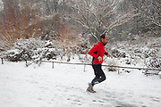 London, UK. Sunday 20th January 2013. Snow fall covering St James's Park, the oldest Royal Park in London. People come out to enjoy this winter scene including jogging for exercise.
