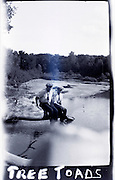 deteriorating photo of two men sitting on rock by water edge 1920s USA