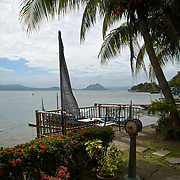Beneath the shaded edge of the Taal Lake Yacht Club with the cone of the Taal Volcano in the near distance.