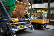 Works lorries including a skip carrier fill the street outside a Subway sandwich shop in London, United Kingdom. A great deal of construction in the capital means that the roads are often full of heavy good vehicles, which is a road safety concern for many other road users.