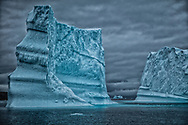 Towering icebergs stand tall and in solitude guarding the old world.