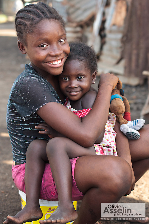 A girl holds a younger child on her lap in the Clara town slum in Monrovia, Montserrado county, Liberia on Thursday April 5, 2012.