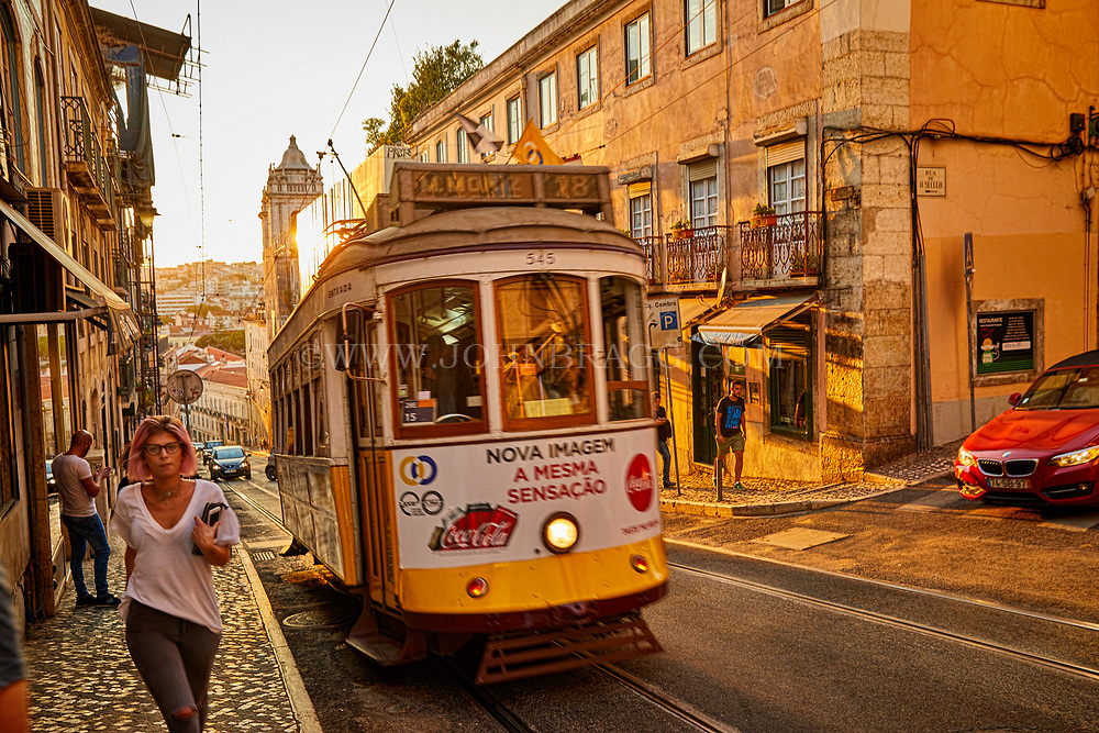 The late afternoon sun sets on a trolley as it moves through Lisbon, Portugal