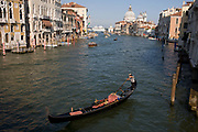 Empty gondola on Venice's Grand Canal seen from Ponte Accademia. The first mention ever of an Italian gondola was in Venice in 1094 and, of course, there have been gondoliers as long as there have been gondolas - so it's one of the oldest professions in the world. Until August 2010, there had never been a single woman gondolier in Venice as licences were always passed down to male family members. Current prices (2015) is 80 Euros for a 40-minute journey (earning them approx 130,000 Euros a year) along the waterways of this old city but rarely do gondoliers wear their straw hat.