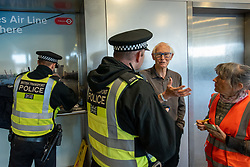 © Licensed to London News Pictures. 10/10/2019. London, UK. As Extinction Rebellion protesters block the entrance to London City Airport an elderly man is arrested by British Transport Police. Protesters arrived via the Docklands Light Rail and proceeded to conduct a sit-in to block the entrance from the train station to the airport. Photo credit: Peter Manning/LNP