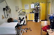 Nederland, Nijmegen, 11-7-2005Een arts, huisarts, van de huisartsenpost, huisartsendienst, pakt verbandmiddelen uit een kast in de spreekkamer. Avonddienst, bereikbaarheid, spoedgeval, ongelukje. Gezondheidszorg, eerstelijns zorg. Zorgverzekeraar, zorgverzekering. Basispakket. Basisverzekering.Foto: Flip Franssen