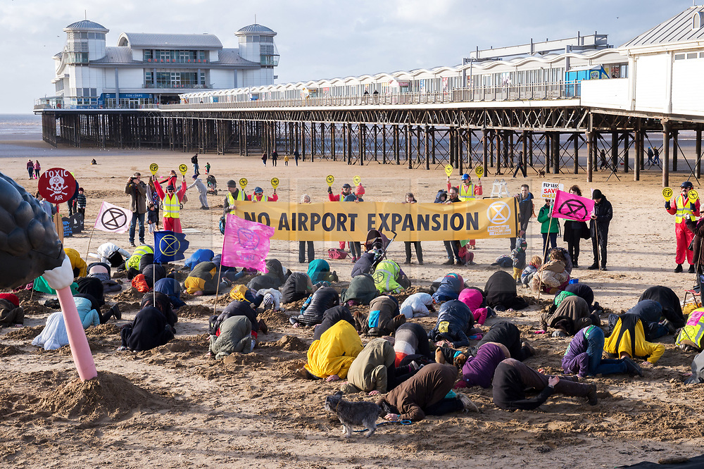 """© Licensed to London News Pictures. 08/02/2020. Weston-super-Mare, North Somerset, UK. """"No Bristol Airport Expansion"""" weekend of protest in Weston-super-Mare, where North Somerset Council will decide on Monday 10 February whether to approve expansion plans for Bristol Airport which is situated in the local authority area of North Somerset. Picture a model ostrich with its head in the sand, joined by 100 other XR protestors with their heads in the sand. Bristol Airport Action Network (BAAN) is staging a 3 day peaceful vigil outside the Town Hall that will lead up to and include the time of the Planning Committee meeting on Monday at 6pm. Events include a beach art action, street theatre, and protest march. The event is co-hosted by Extinction Rebellion groups from Weston, Bristol and other groups around the region who oppose the expansion of Bristol Airport. Bristol Airport, situated in North Somerset, has plans to increase capacity for 12 million passengers a year, up from its current capacity of 10 million by 2026, and their application is due to be considered at a special meeting of North Somerset's Planning and Regulatory Committee on February 10. North Somerset Council officers have recommended the application be approved despite more than 5,400 objections and around 2,200 letters of support. Objections have highlighted the detrimental effects for the local communities including increased air and noise pollution, increased traffic congestion and the loss of Greenbelt land around the airport, but the urgent need to tackle climate change is one of the main reasons why people are objecting. Photo credit: Simon Chapman/LNP."""