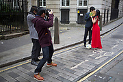 Asian photographer photographing a Chinese couple for their wedding pictures. London, UK. This is a common sight as couples from Asia have their photographs done as before their actual wedding day wearing their dress and suit.