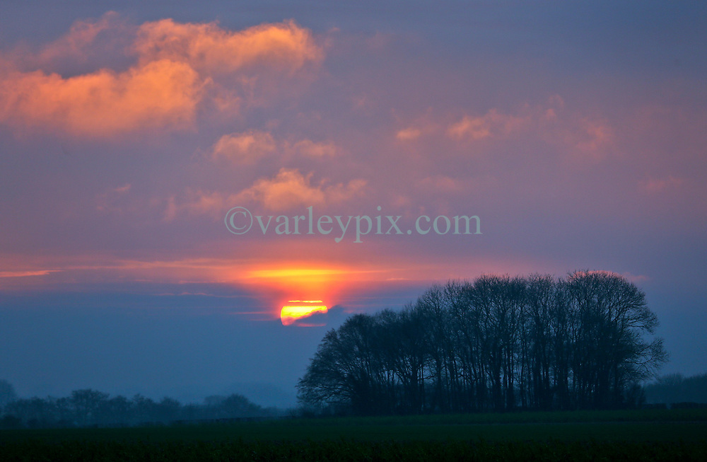 16 Jan 2017. Picardie, France.<br /> The sun drops behind an envelope of cloud at sunset on the road to Vron in Picardy in northern France.<br /> Photo ©; Charlie Varley/varleypix.com